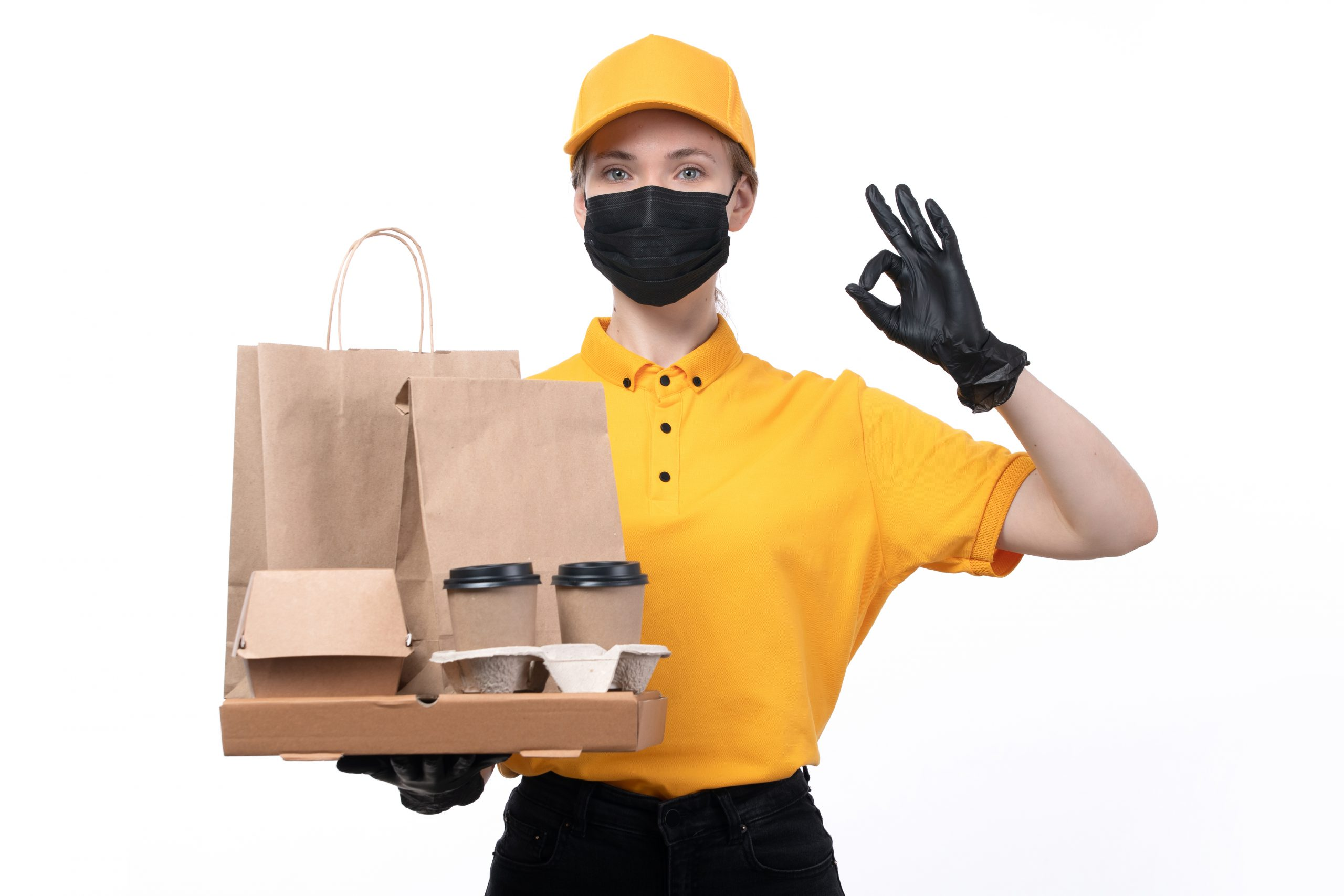 """front view young female courier yellow uniform black gloves black mask holding coffee cups food delivery packages scaled - บรรจุภัณฑ์ กับบทบาทหลากมิติ """"ให้"""" ประโยชน์มากกว่าที่คิด"""